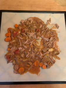 Spreading stew on dehydrator tray.