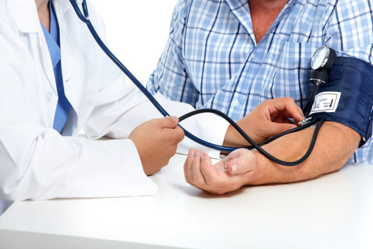 Image of a doctor testing a man's blood pressure, who may need acupuncture and Chinese herbal medicine to manage his condition.