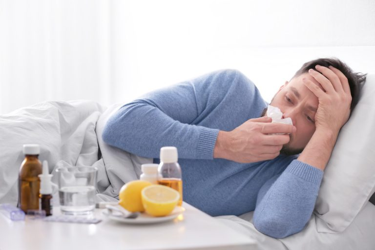 Image of a sick Portland man in bed with tissues and cold medications who should have used acupuncture and herbs and avoided the flu vaccine.